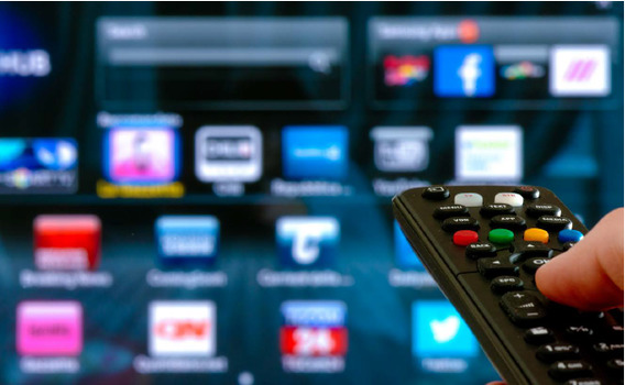 A television remote control points at a smart TV